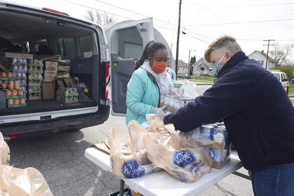 RIGHT: Cierra Thomas, left, youth assistant director, and Lois Ehinger, director of youth department, both with Wellspring Interfaith Social Services,  bag supplies at the Adams Township trustee's office in New Haven on Tuesday.