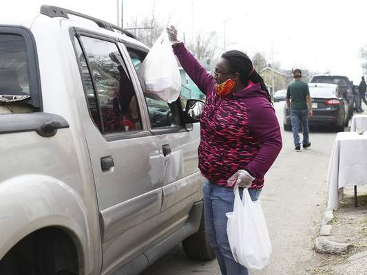 Katie Fyfe | The Journal Gazette  Sheena Greene, founder of Black Women of Excellence,hands offshopping bagsSunday during the Southeast Curbside Community Barbecue at Big Momma's Kitchen. Masks, sanitary gloves, toilet paper, water bottles and dinners were distributed.