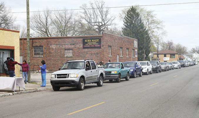 Katie Fyfe | The Journal Gazette  Cars line Oxford Street on Sunday for the free Southeast Curbside Community Barbecue at Big Momma's Kitchen. Masks, sanitary gloves, toilet paper, water bottles and dinnerswere distributed.