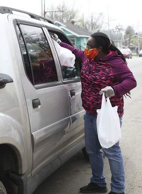 Katie Fyfe | The Journal Gazette  Sheena Greene, founder of Black Women of Excellence,hands off a package Sunday during the Southeast Curbside Community Barbecue at Big Momma's Kitchen. Facial coverings, sanitary gloves, toilet paper, water bottles and dinners were distributed.