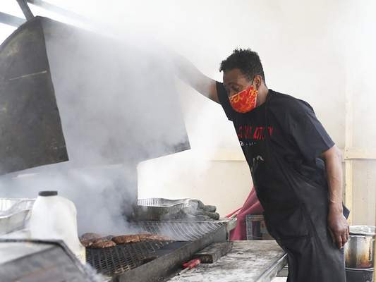 Katie Fyfe | The Journal Gazette  Greg Hunter prepares hamburgers Sunday during the Southeast Curbside Community Barbecue at Big Momma's Kitchen.