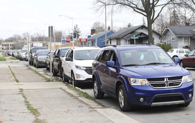 Katie Fyfe | The Journal Gazette  Cars line up Sunday along Oxford Street for the free Southeast Curbside Community Barbecue at Big Momma's Kitchen.Facial coverings, sanitary gloves, toilet paper, water bottles and dinners were distributed.