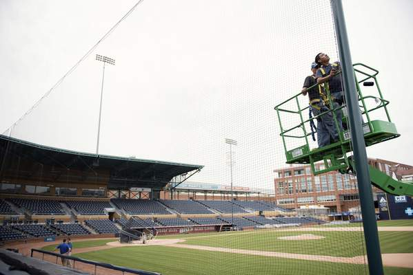 Associated Press/File In this March 31, 2016, file photo, Elias Ruiz, front right, and Steven Woytysiak, both from C&H Baseball, help install a 35-foot-high safety netting that runs behind home plate and along the length of each dugout at the Durham Bulls Athletic Park in Durham, N.C.