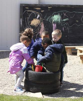 Katie Fyfe   The Journal Gazette Four children play together Monday on the playground at Early Childhood Alliance.