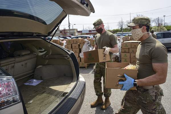 Photos by Mike Moore | The Journal Gazette Members of the Indiana National Guard's 1st Battalion, 293rd Infantry Regiment load food into vehicles Monday during the Community Harvest Farm Wagon  distribution at Parkview Field.