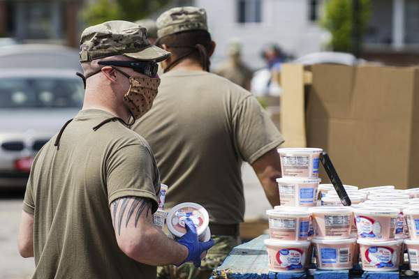 Mike Moore | The Journal Gazette Members of the Indiana National Guard load food into vehicles on Monday during a Community Harvest Food Bank distribution outside Parkview Field.