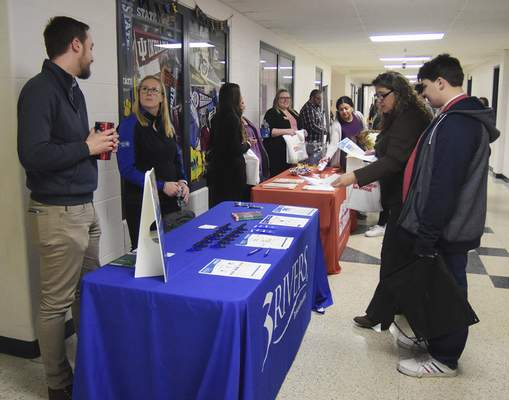Katie Fyfe | The Journal Gazette  Parents and students stop at the 3Rivers and 1st Source Bank booths for college financial options during the Homestead College Fair at Homestead High School on Monday, March 9th, 2020.