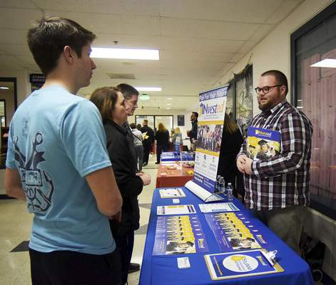 Katie Fyfe | The Journal Gazette  John Sheets, a junior in high school, talks to INvested representative Alex Samuel at the INvested booth with his parents Alison Sheets and Rick Sheets during the college fair at Homestead High School on Monday, March 9th, 2020.