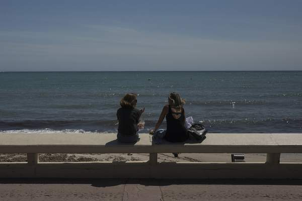 Two women sit above the deserted Croisette beach due to measures put in place to stop the spread of the coronavirus in Cannes, southern France, Tuesday, May 12, 2020. The Cannes Film Festival won't kick off as planned on Tuesday. The festival's 73rd edition has been postponed indefinitely, part of the worldwide shutdowns meant to stop the spread of the coronavirus. (AP Photo/Daniel Cole)
