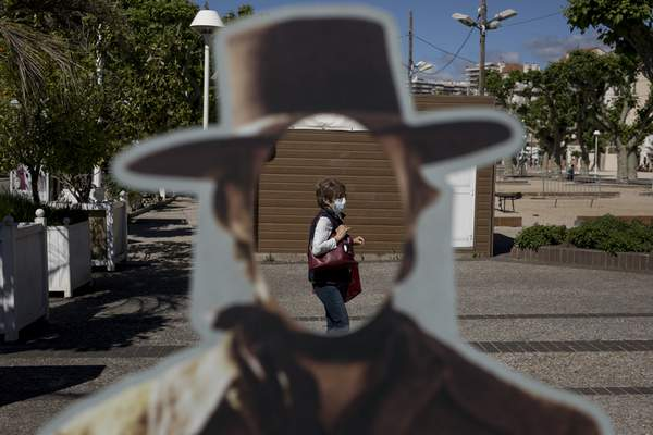 A woman wearing a face mask to protect against coronavirus is pictured through a hole in a cardboard cut out of actor Clint Eastwood in Cannes, southern France, Tuesday, May 12, 2020. The Cannes Film Festival won't kick off as planned on Tuesday. The festival's 73rd edition has been postponed indefinitely, part of the worldwide shutdowns meant to stop the spread of the coronavirus. (AP Photo/Daniel Cole)