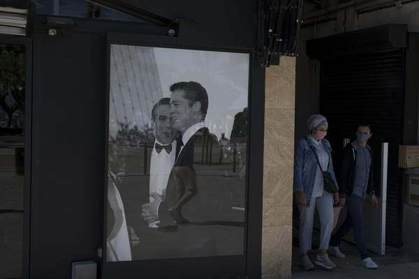 A couple wearing masks to protect from coronavirus walk by a poster of Brad Pitt and George Clooney in Cannes, southern France, Tuesday, May 12, 2020. The Cannes Film Festival won't kick off as planned on Tuesday. The festival's 73rd edition has been postponed indefinitely, part of the worldwide shutdowns meant to stop the spread of the coronavirus. (AP Photo/Daniel Cole)