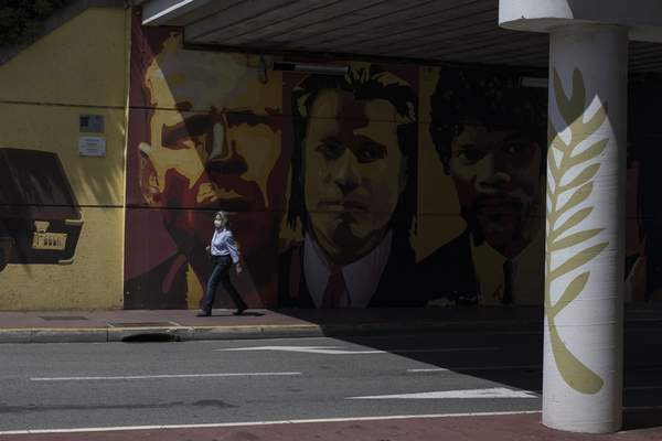 A woman wearing a face mask to protect against coronavirus walks by a mural depicting characters from the film Pulp Fiction in Cannes, southern France, Tuesday, May 12, 2020. The Cannes Film Festival won't kick off as planned on Tuesday. The festival's 73rd edition has been postponed indefinitely, part of the worldwide shutdowns meant to stop the spread of the coronavirus. (AP Photo/Daniel Cole)
