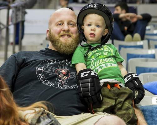 Josh Gales | Special to The Journal Gazette Moore poses with his youngest son, Basil, 2, at a Komets game.