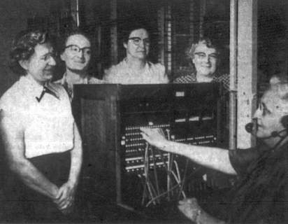 No Title Woodburn's five phone operators gather around the switchboard to talk over old times in 1954. Working the board is Mrs. Mildred Westerlin. Standing, from the left, are Mrs. Lila Rosener, Mrs. Edith Wooten, Mrs. Hilda Roemke and Mrs. Anna Langhan. (Journal Gazette file photo) (User: Windows NT/95/98 User)