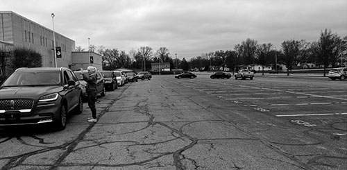Photos courtesy Wellspring Wellspring food bank director Linda Hansen directs drivers lined up for a food-pantry event at Bishop Dwenger High School on March 31.
