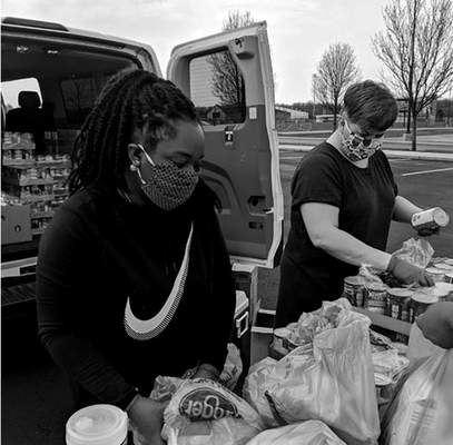 Canned goods and other foodstuffs are bagged by Cierra Thomas, left, and Lois Ehinger for giveaway at a Wellspring event on April 7 at Carroll High School.