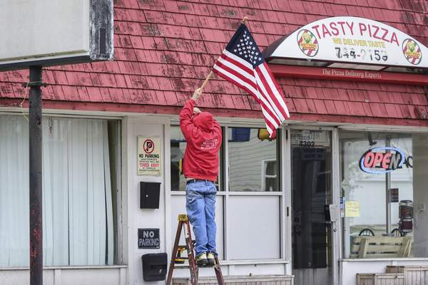 Mike Moore | The Journal Gazette  Tasty Pizza owner Matthew Whitacre hangs a flag outside his restaurant Monday on Fairfield Ave.
