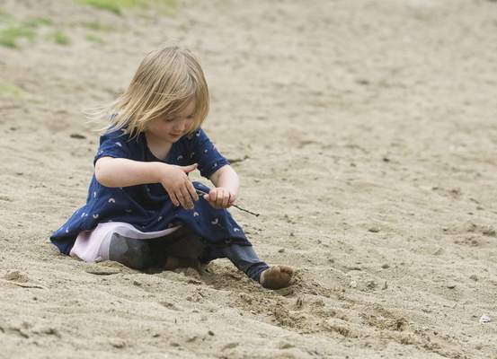 Michelle Davies | The Journal Gazette Tabitha Dunwoody, 3, of Fort Wayne, plays in the sand at Bowman Lake at Fox Island Thursday morning.
