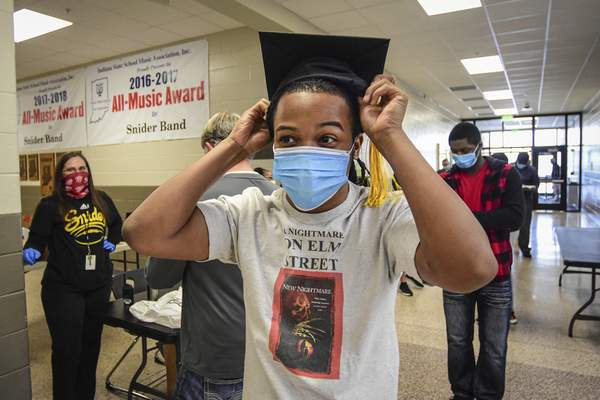 Mike Moore | The Journal Gazette  Graduating senior Donovan Eley tries on his graduation cap Thursday for the first time at Snider High School.