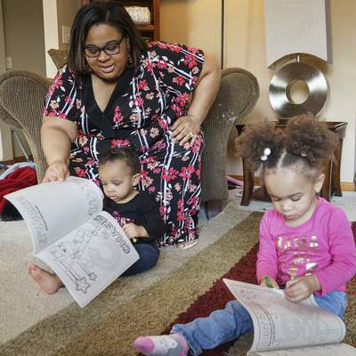 Mike Moore | The Journal Gazette  Kaylece Guy, 2, right and sister Adaya Guy, 1 color for their mother, Kela Guy, on Sunday while spending Mother's Day in their home.