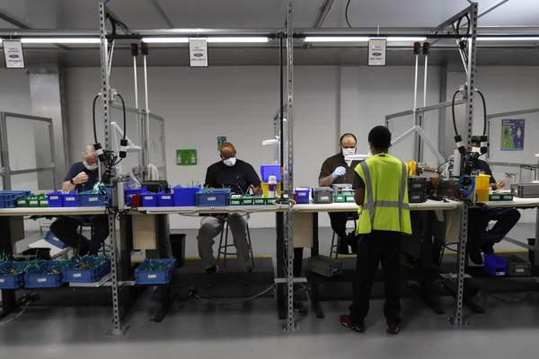 Associated Press photos Ford Motor Co. team leader Stephon Robinson, front, oversees workers on the subassembly line of ventilator production Wednesday in Ypsilanti Township, Mich.