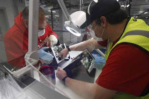 Ford Motor Co. team leader Kyle Lenart, right, inspects a ventilator that the automaker is assembling Wednesday at the plant in Ypsilanti Township, Mich.