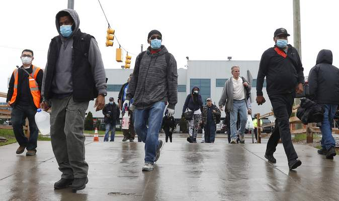 Associated Press United Auto Workers members leave the Fiat Chrysler Automobiles plant Monday after employees returned to work for this first time in nearly two months in Warren, Mich.