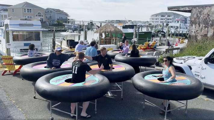 In this image made from Saturday, May 16, 2020, video provided by Revolution Event Design & Production, bumper tables, created by the company and designed to allow people to practice social distancing while eating and talking, are debuted at Fish Tales, a restaurant in Ocean City, Md. (Katie Kirby/Revolution Event Design & Production via AP)