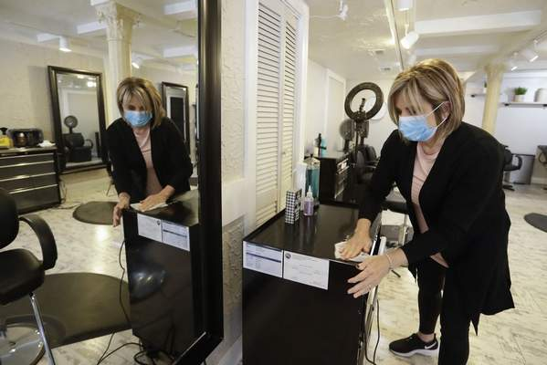 Kimberly Hubbard cleans her station at Kimberley Hair Design, Saturday, May 9, 2020, in Zionsville, Ind. (AP Photo/Darron Cummings)