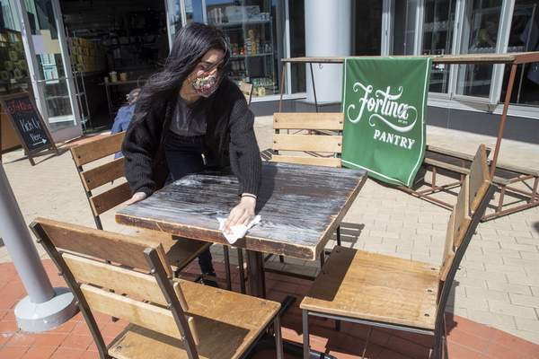 An employee at Fortina restaurant in Stamford, Conn., disinfects an outdoor table Wednesday in preparation for the opening of outdoor dining.