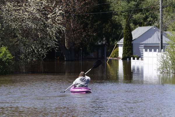 Associated Press A kayaker paddles out to check on a residence as the Tittabawassee River overflows Wednesday in Midland, Mich., forcing thouands to evacuate.