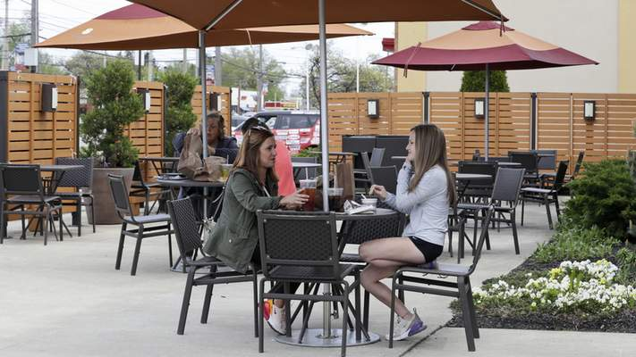 Melissa and Lexie Hoinski have lunch at an outdoor restaurant, Wednesday, May 20, 2020, in Mayfield Heights, Ohio. (AP Photo/Tony Dejak)