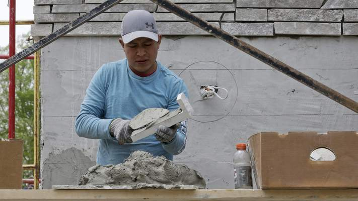 Francisco Hernandez puts concrete on a brick to be added to the outside of a new home, Wednesday, May 20, 2020, in Chagrin Falls, Ohio. (AP Photo/Tony Dejak)
