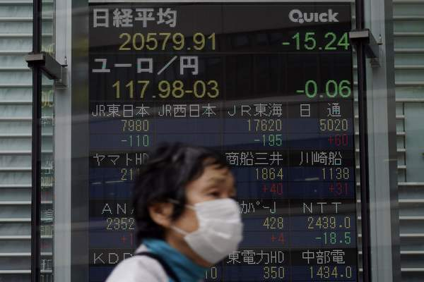 A masked woman walks past an electronic stock board showing Japan's Nikkei 225 index at a securities firm in Tokyo Thursday, May 21, 2020. (AP Photo/Eugene Hoshiko)