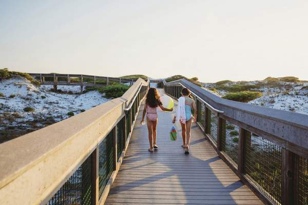 In this June 1, 2019, photo provided by the Florida Department of Environmental Protection, beachgoers walk on a boardwalk at Grayton Beach State Park in Santa Rosa Beach, Fla. (Courtesy of Florida Department of Environmental Protection via AP)