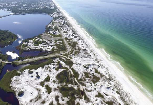 This Aug. 1, 2018, aerial photo made available by the Florida Department of Environmental Protection shows Grayton Beach State Park in Santa Rosa Beach, Fla. (Running Man Pictures/Courtesy of Florida Department of Environmental Protection via AP)