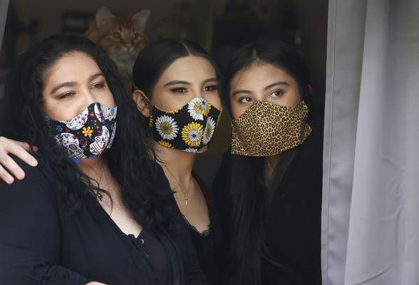 In this Monday, May 18, 2020, photo, Anissa Archuleta, center, sits at a window with her sister Alexis Archuleta, right, and her mother, Jaime Ortega, at their home in Midvale, Utah. (AP Photo/Rick Bowmer)