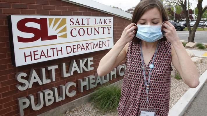 In this Tuesday, May 19, 2020, photo, health investigator Mackenzie Bray adjusts her mask at the Salt Lake County Health Department, in Salt Lake City. (AP Photo/Rick Bowmer)