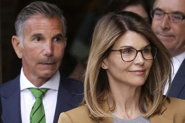 FILE - In this April 3, 2019, file photo, actress Lori Loughlin, front, and her husband, clothing designer Mossimo Giannulli, left, depart federal court in Boston after a hearing in a nationwide college admissions bribery scandal. (AP Photo/Steven Senne, File)