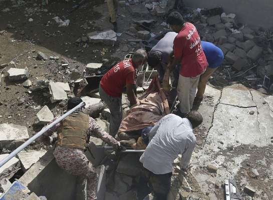 Volunteers carry the dead body of a plane crash victim at the site of a crash in Karachi, Pakistan, Friday, May 22, 2020. (AP Photo/Fareed Khan)