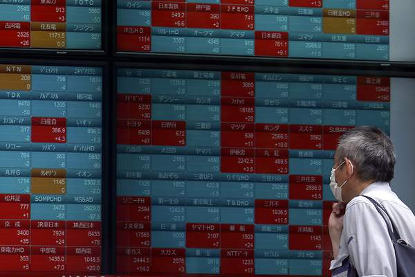A man looks at an electronic stock board showing Japan's Nikkei 225 index at a securities firm in Tokyo Friday, May 22, 2020. Shares are slipping in Asia as tensions flare between the U.S. and China and as more job losses add to the economic fallout from the coronavirus pandemic. (AP Photo/Eugene Hoshiko)