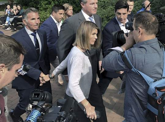 FILE - In this Aug. 27, 2019, file photo, Lori Loughlin departs federal court with her husband, clothing designer Mossimo Giannulli, left, in Boston, after a hearing in a nationwide college admissions bribery scandal. Loughlin and Giannulli have agreed to plead guilty in a video arraignment scheduled for Friday, May 22, 2020, to charges of trying to secure the fraudulent admission of their two children to the University of Southern California as purported athletic recruits. (AP Photo/Philip Marcelo, File)