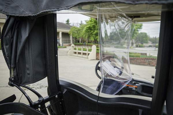 Mike Moore | The Journal Gazette A plastic divider separates passengers using golf carts at Autumn Ridge Golf Course on Auburn Rd. on Wednesday 05.20.20