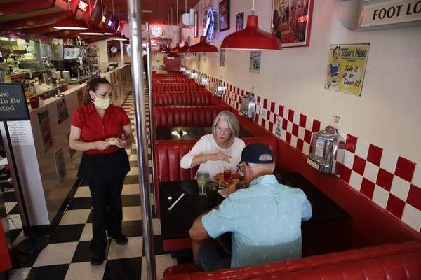Lynn and Ryan Tanner are served lunch at a diner Thursday in Ventura, Calif. Nearly 6 in 10 Americans say they won't venture to restaurants anytime soon.