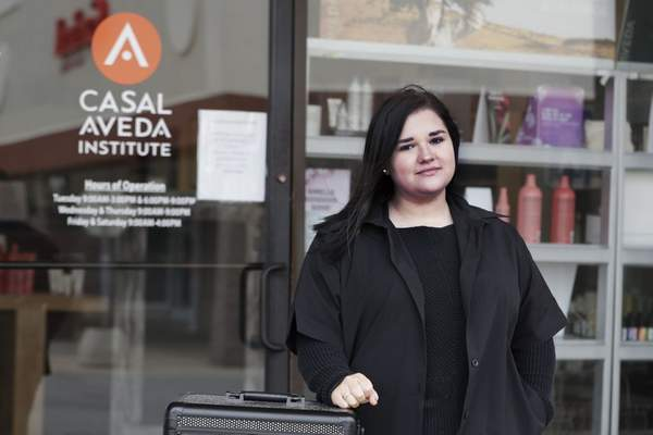 In this Friday, May 8, 2020 photo, Christa Schall poses outside her cosmetology school, Casal Avedo Institute, in Austintown, Ohio. (AP Photo/Tony Dejak)