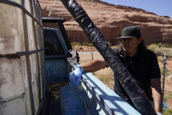 In this April 27, 2020, photo, Chris Topher Chee waits for water to fill a tank in the back of his truck to haul home in Oljato-Monument Valley, Utah, on the Navajo reservation. (AP Photo/Carolyn Kaster)