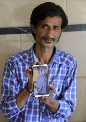 Pakistani Shahid Ahmed shows the picture of his mother Irshad Begum, who was killed in the Friday's plane crash, on his mobile phone outside a morgue in Karachi, Pakistan, Saturday, May 23, 2020. (AP Photo/Fareed Khan)