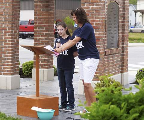 Katie Fyfe   The Journal Gazette  Kaitlynn Baxter, 11, reads her letter to Mayor Joe Kelsey on Saturday about why she believes there should be a wishing stone in the town of Woodburn with her teacher Joni Price by her side. during the dedication ceremony for The Woodburn Wishing Stone was dedicated at the Woodburn Clock Tower Plaza as part of the students' efforts.