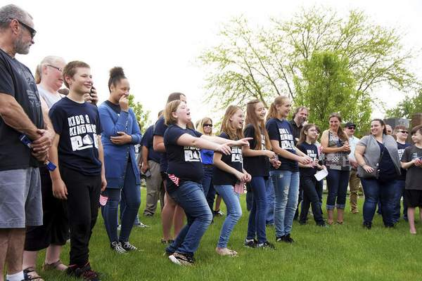 Katie Fyfe   The Journal Gazette  Woodlan Elementary teacher JoniPrice's fifth grade class shows off a theme song they have for when her husband would call into class during the dedication day for the Woodburn Wishing Stone on Saturday.