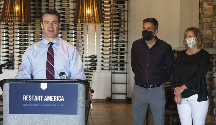 Michelle Davies | The Journal Gazette U.S. Sen. Todd Young, R-Ind.,discusseshis RESTART Act on Tuesday at Catablu Grille, withCatablu owners Michael and Maureen Catalogna looking on.